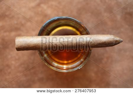 Cuban Cigar. Hand Rolled Cuban Cigar on a Glass of Whiskey on top of a Leather Table. Room for text overlay.