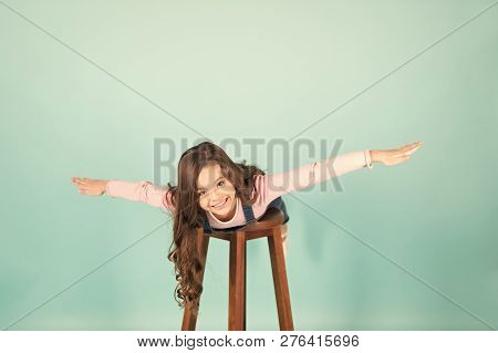 Happy Child Flying On Chair, Imagination. Small Girl With Long Hair Play Pilot, Adventure. Imaginati