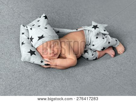 Cute little baby in hat and pants with stars pattern sweetly sleeping on gray blanket