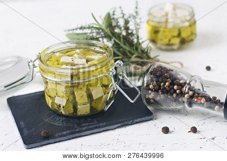 Marinated Feta In A Glass Jar And Spices Against White Background