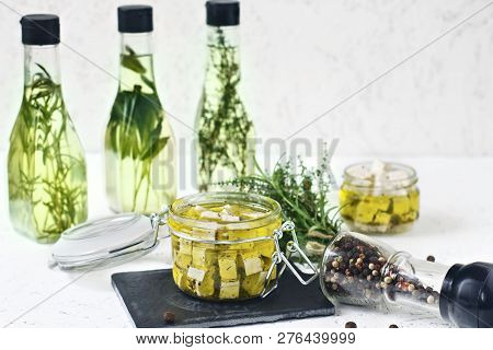 Marinated Feta In A Glass Jar, Spices And Flavored Olive Oil On A Wooden Background