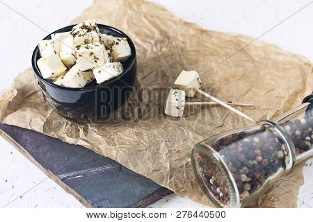 Marinated Feta In A Plate On A Wooden Board With Spices On A White Background