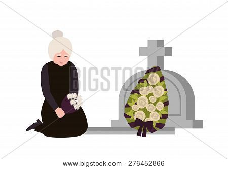 Sorrowful Elderly Woman Dressed In Mourning Clothes Crying Near Grave With Headstone And Wreath. Sad