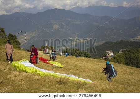 Pokhara/nepal - 2.11.2018: Paragliders On The Hillside Train To Fly Against The Backdrop Of A Green