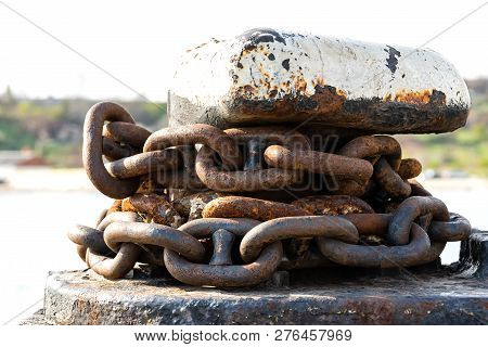 Rusty Anchor Chain Around The Mooring Bollard