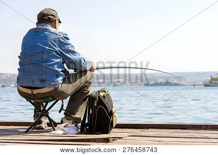 Fisherman Catches Fish From The Dock In The Port