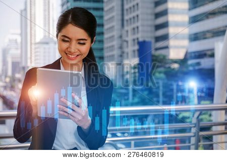 Young Asian Investor Business Woman Smiling And Looking Mobile Tablet With Graphic Candle Stick Grap