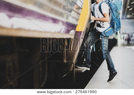 Young Asian Traveler With Backpack In The Railway, Traveler Holding And Stepping Up To A Train With
