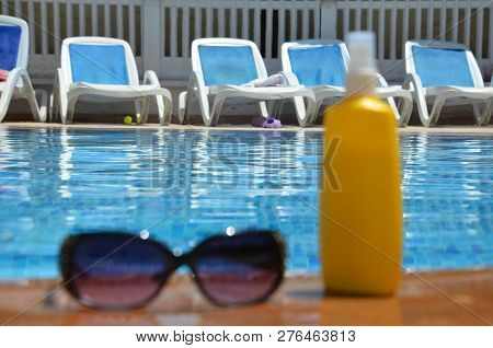 Sunglasses And Yellow Sunscreen Near A Blue Pool Outside. Concept Of Vacation, Vacation, Summer At T