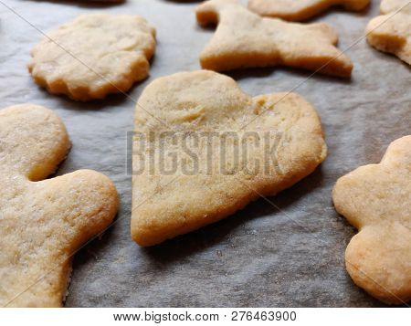 closeup of homemade baked cookies on a baking tray with heart shaped cookie in the middle