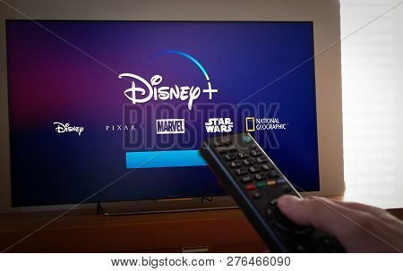 Barcelona, Spain. Jan 2019: Man Holds A Remote Control With The New Disney+ Screen On Tv. Disney+ Is