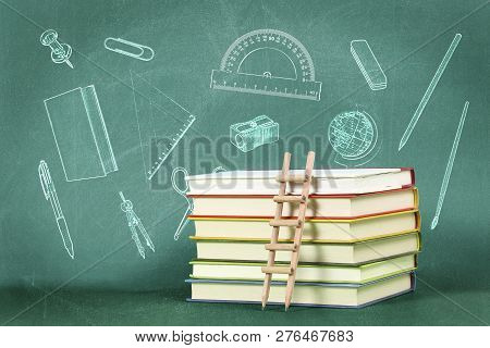 Education Concept With Pencil Ladder On Stack Of Books Against Green Chalkboard