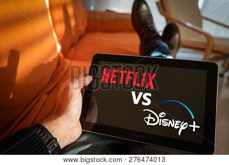 Barcelona, Spain. January 2019: Man Holds A Tablet With Netflix Vs Disney+ Application Logo On Scree