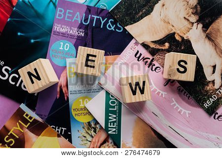 Top View Of Pile Of Different Tabloid Magazines And Wooden Cubes With Word News On Surface