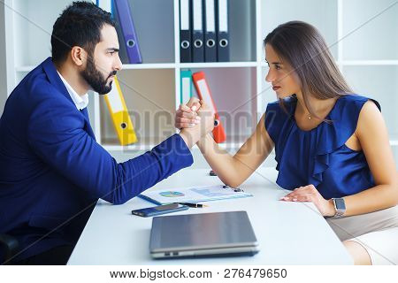 Side view portrait of man and woman armwrestling, exerting pressure on each other, looking eyes in eyes, struggling for leadership. Business, society concept photo poster