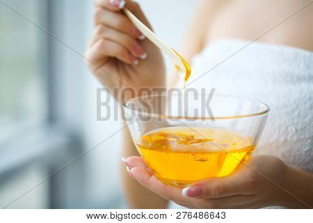 Women hold orange paraffin wax bowl. Woman in beauty salon poster