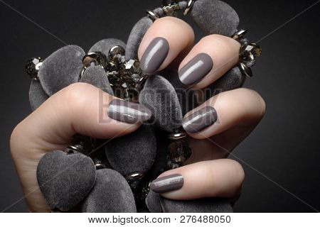 Female Hand With Gray Nails Is Holding A Gray Decoration On Dark Gray Background, Manicure And Nail