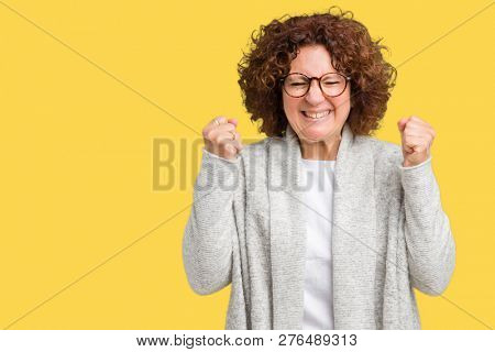 Beautiful middle ager senior woman wearing jacket and glasses over isolated background excited for success with arms raised celebrating victory smiling. Winner concept.