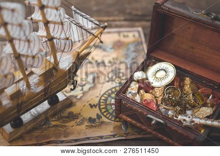 Pirate Ship, Treasure Map, Treasure Chest Full Of Gold On Wooden Table Background.