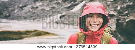 Active outdoors people lifestyle - happy hiker Asian woman laughing in the rain on mountain hike - Outdoors adventure trek activity, wearing waterproof raincoat sportswear clothes. Banner panorama.