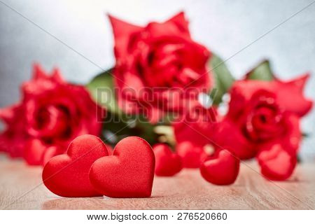 Valentine background with red satin hearts. Selective focus on two big hearts. Valentine's Day card. Design element for romantic greeting card, wedding invitation,