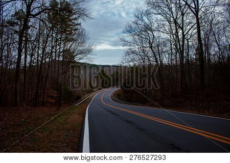 A Winding Road Curves Through The Bare Woods During Winter.