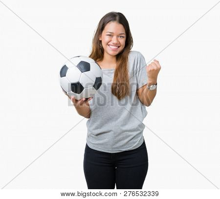 Young beautiful brunette woman holding soccer football ball over isolated background screaming proud and celebrating victory and success very excited, cheering emotion