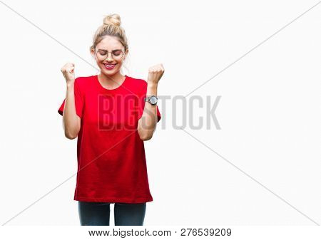 Young beautiful blonde woman wearing red t-shirt and glasses over isolated background excited for success with arms raised celebrating victory smiling. Winner concept.