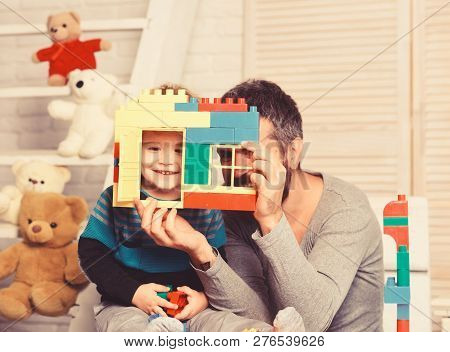 Dad And Kid With Toys On Wooden Background Hold House Wall Made Of Plastic Blocks. Father And Son Wi