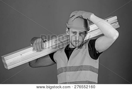 Wooden Materials Concept. Man In Helmet, Hard Hat And Protective Gloves Holds Wooden Beam, Grey Back