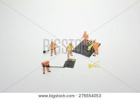 A Mini Worker Working On Micro Sd Card.