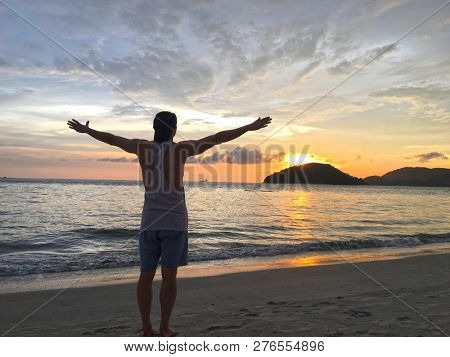 Man meditating whilst raising his arms an looking out to sea at the beautiful sunset on Pantai Cenang on Langkawi Island in Malaysia