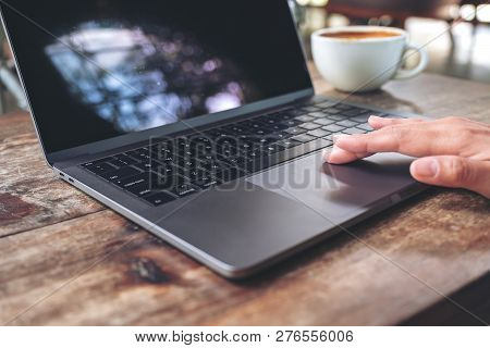 Closeup Image Of Hand Using And Touching On Laptop Touchpad On Wooden Table