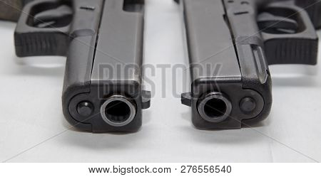Two black semi automatic pistols, a 9mm and a 40 caliber with one on top of the other on a white background poster