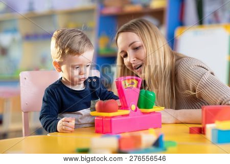 Little Child Boy And Nursery Teacher Sit At Table And Play With Toy Scales In Kindergarten Playroom