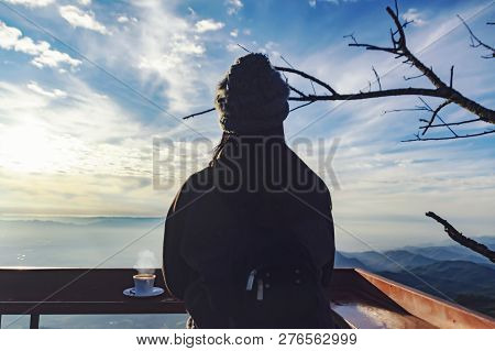 Woman Traveler Drinks Coffee In Restaurant With A View Of The Mountain Landscape. A Young Tourist Wo