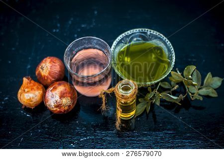 Close up of caster oil,onion juice mixture used to make hair stronger and thicker on wooden surface.; poster
