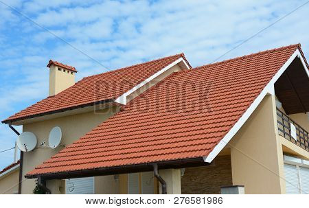 Modern House With Chimney, Red Clay Tiled Roof And Gable And Valley Type Of Roof Construction. Build