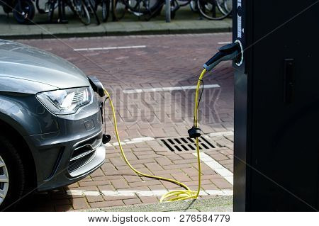 Electric Car Charging On Parking Lot With Electric Car Charging Station On City Street. Electric Car