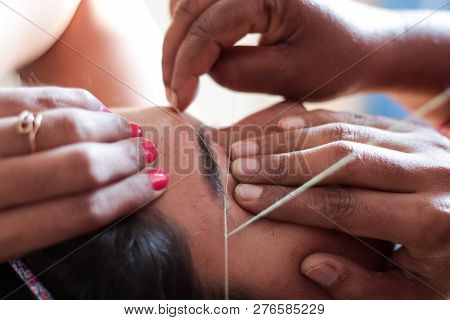 Shaping And Plucking Of Eye Brow With Threading. Epilation Cosmetic Procedure In Beauty Parlour.