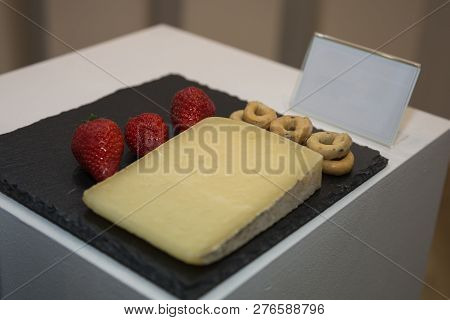 Slice Of Sheep's Cheese On Black Tablecloth Decorated With Italian Taralli And Strawberries