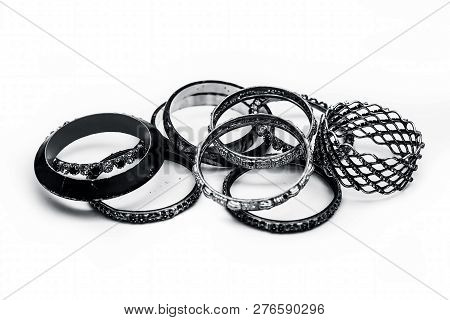 Close up of mixed ornaments or jeweleries to wear them in hands isolated on white which are bangles and some other band like objects. poster