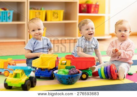 Group Of Babies Is Playing On Floor In Nursery Or Creche. Children In The Day Care Center. Fun In Th