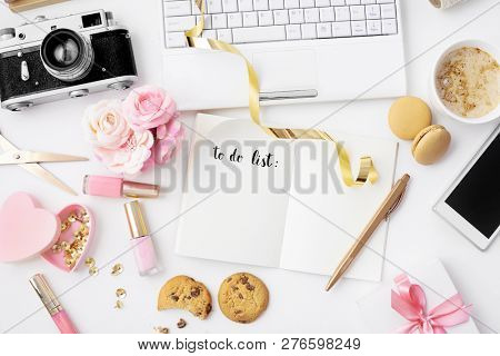 workspace with notebook keyboard, to do list, planner, organizer, photo camera, smartphone, open sketchbook, diary, coffee on white background. Flat lay, top view office table desk.