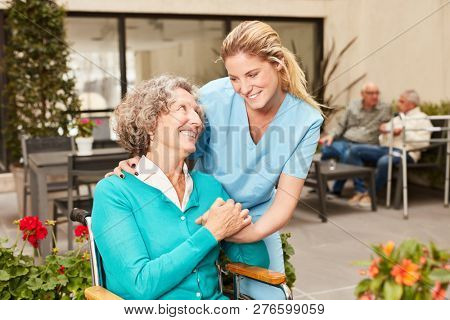 Caring caregiver takes care of senior woman on terrace in retirement home