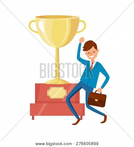 Man In Suit Showing Yes Gesture, Big Golden Trophy Cup On Background. Excited Worker Achieved Succes