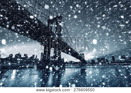 Black And White Image Of Manhattan Skyline And Manhattan Bridge At Night During A Snowfall.