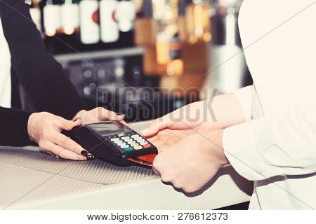 Credit Card Payment And Electronic Bank Concept. Cashiers Hand Holds Credit Card Terminal On Defocus