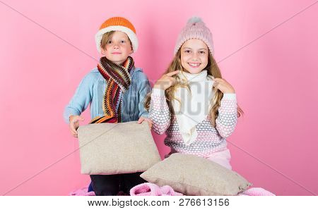 Children Boy And Girl Warm Up With Pillows And Hats. Stay Warm And Comfortable. Warm Up Your Winter