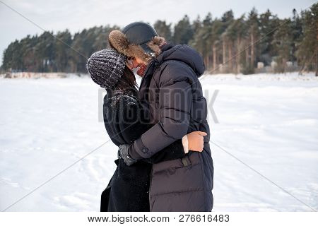 Young Millennial Couple In Love Embracing In Winter Park Outdoor. Sensual Tender Boyfriend And Girlf